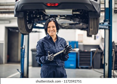 Auto car repair service center. Happy female mechanic standing by the car