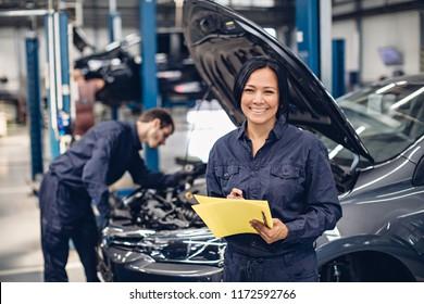 Auto car repair service center. Two mechanics - man and woman examining car engine