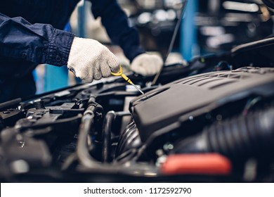 Auto car repair service center. Mechanic checking engine oil level