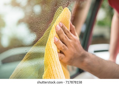 Auto care service staff cleaning car window glass with microfiber cloth