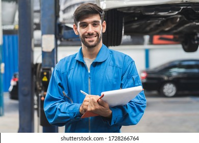 Auto check up and car service shop concept. Mechanic writing job checklist to clipboard to estimate repair quotation to client at workshop garage.