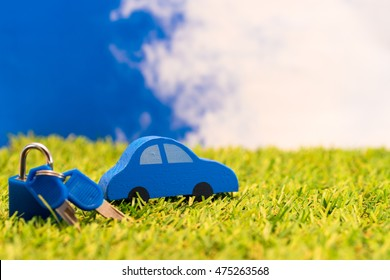 Auto concept.  Colorful toy car on grass against blue sky