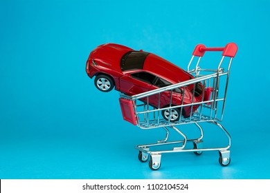 auto dealership and rental car concept.  red car shopping cart blue background