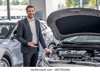 Auto dealership. Smiling brown-haired male pointing at open car hood in showroom