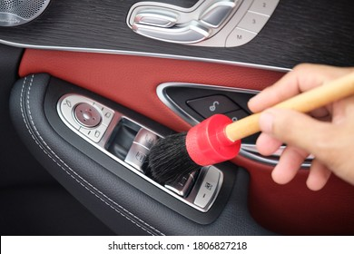 Auto detailer using detailing brush for cleaning dust in car window switch. Male hand cleaning car interior & upholstery with detail brush. Focus on brush. Car detailing concept. Car wash background.