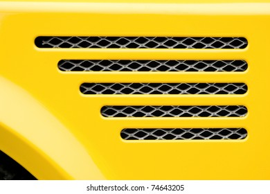 auto engine grille closeup on a bright yellow vehicle