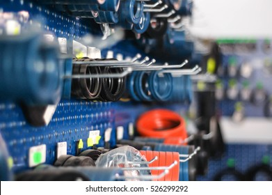 Auto and heavy vehicles store shelf with assortment of colorful rubber gaskets hanging from a blue wall rack. Depth of field bokeh effect.