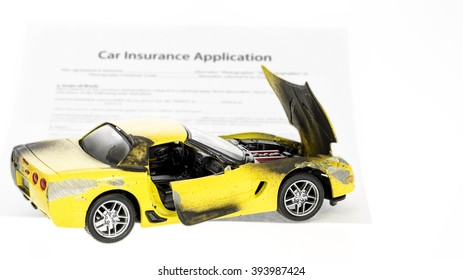 Auto insurance form and car that has been wreaked
