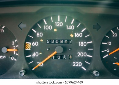 Auto interior dashboard details with indication lamps. Dashboard closeup with visible speedometer and fuel level. Odometer, tachometer. Large kilometer of an old car. Big run of an retro vehicle