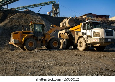 Auto loader is unloading scoop with gravel into dump truck.