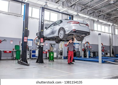 Auto maintenance. The master replaces the oil, checks the wheels, Repair of brake system on car wheels, performs maintenance. Modern universal car center. Shymkent Kazakhstan April 15, 2019