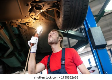 Auto maintenance process. Attentive young bearded repairman in uniform standing under raised car with lamp in his hand