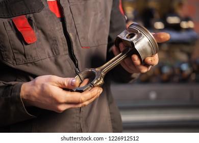 auto maintenance station. mechanic holding piston in hands. engine repair.