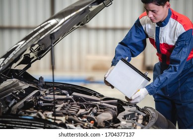 The auto mechanic is about to change a new battery for the customers who come to use the battery replacement service at the shop.