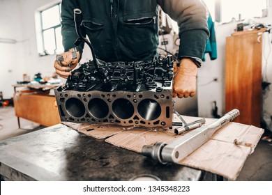 Auto mechanic adjusting cylinder head on engine block at workshop.