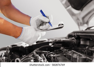 Auto mechanic checking car engine at the garage