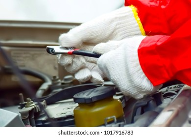 Auto mechanic checking and repair the engine. Auto mechanic checking oil. Selective focus with shallow depth of field.