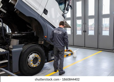 Auto mechanic checking the truck in the garage. Servicing and repairing trucks in a large garage. Car service, diagnostics and truck maintenance
