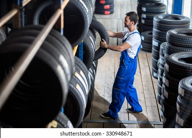 Auto mechanic  choose tire for car at a tire store
