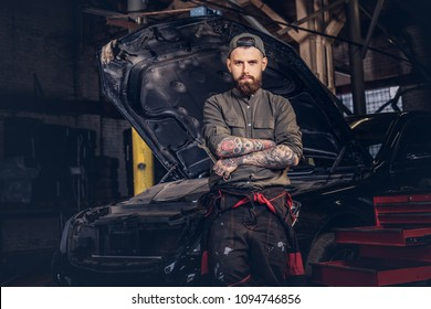 Auto mechanic crossed hands while standing against a car in a repair garage.