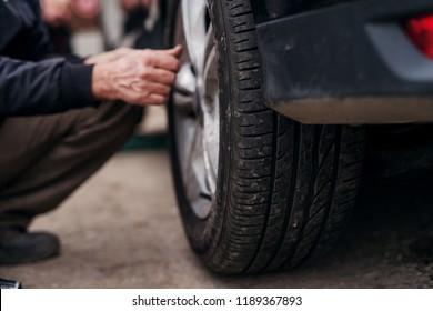 Auto mechanic with electric screwdriver changing tire outside. Car service. Tire installation.