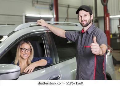 An auto mechanic and female customer in garage