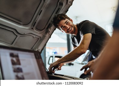 Auto mechanic fixing a vehicle in service station. Car mechanic working at automotive service center looking at his coworker and smiling.