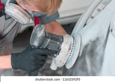 Auto mechanic grinds car part for painting
