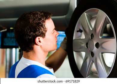 Auto mechanic in his workshop changing tires or rims
