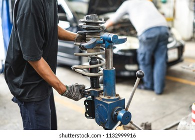 Auto mechanic maintaining a car shock absorbers at garage station.