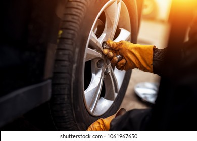 Auto mechanic man with electric screwdriver changing tire outside. Car service. Hands replace tires on wheels. Tire installation concept.