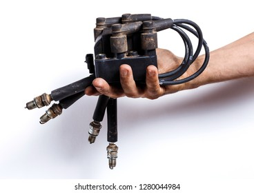 Auto mechanic with old high-voltage wires, spark plugs and ignition coil on the white background. Old car parts in the hand.