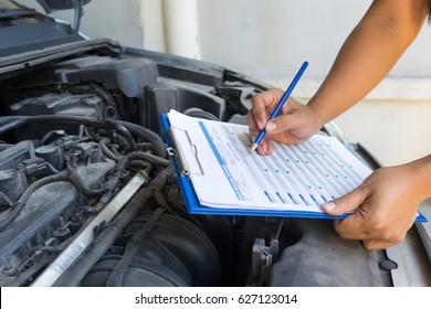 Auto mechanic (or technician) checking car engine at the garage, industrial concept