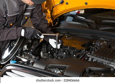 Auto Mechanic performing maintenance on the engine