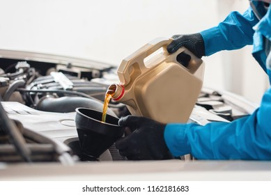 The auto mechanic pours new clean engine oil through the funnel. replacement of engine oil in the machine. car service worker