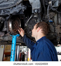 auto mechanic is repairing a car on a hydraulic platform