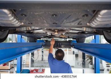 auto mechanic repairman examining automobile car engine at maintenance repair service station garage