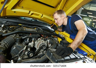 auto mechanic repairman tighten screw with spanner during automobile car maintenance at engine repair service station garage