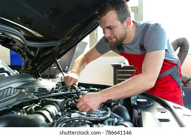 Auto mechanic repairs vehicle in a workshop