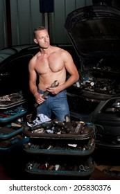 auto mechanic at service station with naked upper body
