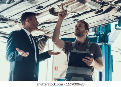 Auto Mechanic Showing Client Car Problem. Buisness Man in Black Suit dont Understand Cause of Breakage. Automobile Master in Uniform Explainig in Garage. Repair Service Concept.