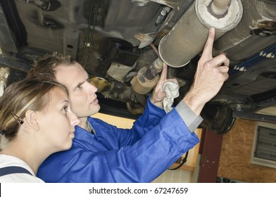 Auto mechanic shows the female trainee maintenance of the Car muffler under a car on a hoist