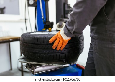 Auto mechanic taking tire.