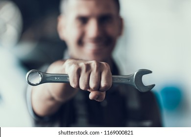 Auto Mechanic with Tool on Blurred Background. Close-up of Repairman Strong Fist Holding Metalic Wrench in Garage. Automobile Repair Service Concept. Automobile Master Concept
