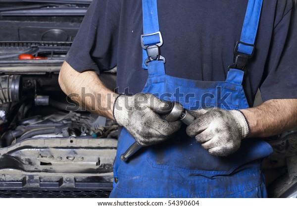Auto mechanic in uniform holding work tool