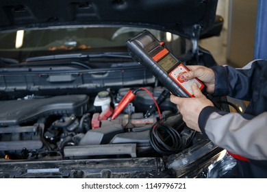 auto mechanic uses multimeter voltmeter to check voltage level in car battery.