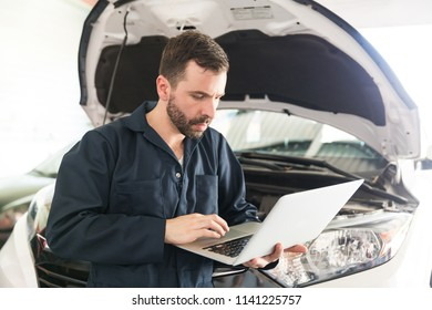 Auto mechanic using computer diagnostic program while repairing car in workshop