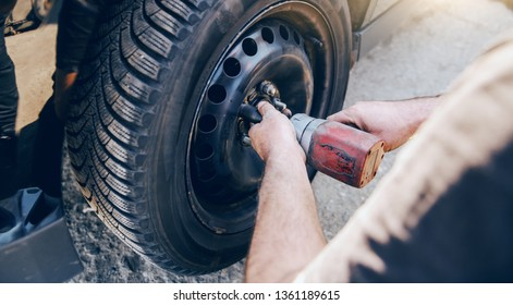 Auto mechanic using tool to change tire while crouching at workshop.