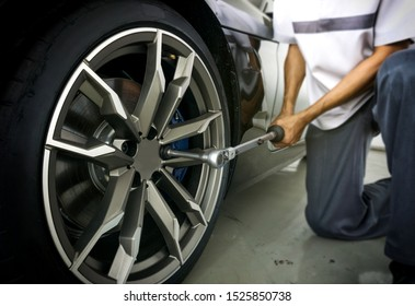 Auto mechanic using Torque wrench to inspection the wheel nuts for safety in travel in mechanics garage. Car repair center.