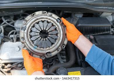 Auto mechanic wearing protective work gloves holding used clutch pressure plate above a car engine